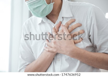 Man wear medical face mask, symptoms of coronavirus diseases, chest pain - heart attack, fever, cough, shortness of breath during work in office, health care concept. Royalty-Free Stock Photo #1747636952