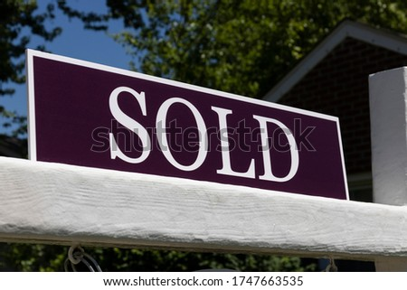 Sold House sign for real estate transaction. Close-up with white letters on purple background.