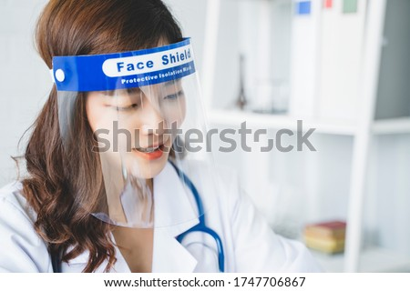 Medical healthcare beautiful Asian doctor wearing face shield mask protection from infectious disease virus bacteria germs coronavirus covid-19, safety protection working in hospital modern office  Royalty-Free Stock Photo #1747706867