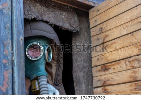 Portrait of a man in a gas mask looking out of the door of a fortified bunker. Background of ecological pollution of the planet with industrial waste or war using nuclear and bacteriological weapons #1747730792