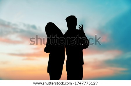 Silhouettes of arguing couple against sunset sky with clouds. Relationship problems #1747775129