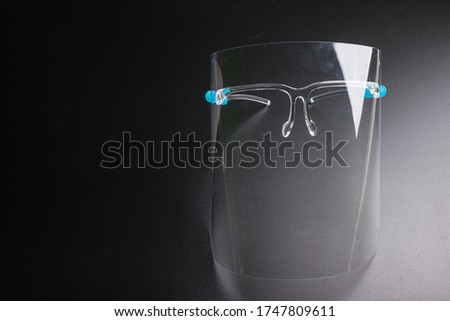 Face shield on a black background. Pandemic COVID-19 virus and protection against coronavirus concept.Concepcion prevent diseases. Royalty-Free Stock Photo #1747809611