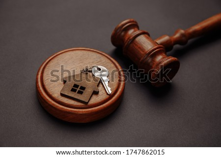 Judge gavel and key chain in shape of two splitted part of house on wooden background. Concept of real estate auction or dividing house when divorce, division of property, real estate, law system #1747862015