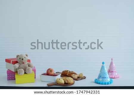Colorful gift boxes placed with a teddy bear Red apples in a white apple tray, bake bread, cream cookies, blue and pink party hat placed on the table, white background #1747942331