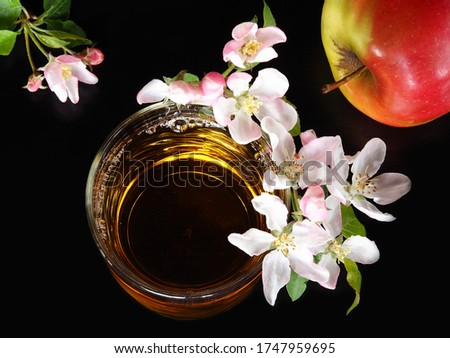 Natural Apple juice in a glass with white apple flowers and an apple on a black background closeup, top view. Bright romantic picture with a drink and blooming for the screensaver, wallpaper