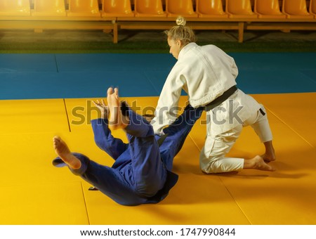 Martial arts. Sparing Portners. Sport man and woman in white and blue kimono train judo throws and captures in the sports hall Royalty-Free Stock Photo #1747990844