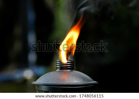 Closeup macro picture of flame burning on top of a kerosine torch with metal threaded top