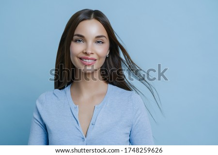 Positive lovely feminine lady happy to have first date with boyfriend, smiles broadly, has appealing appearance, glad to hear something pleasant, models indoor alone, wears blue casual jumper Royalty-Free Stock Photo #1748259626
