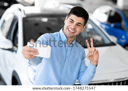 First Car Pic. Handsome young man smiling and taking selfie with victory sign standing in front of his new car at the dealership