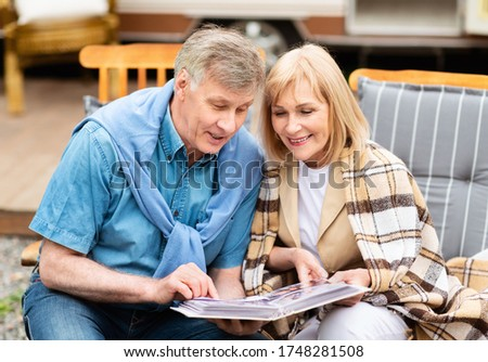 Happy moments. Mature couple admiring photos in family album, remembering their youth at campground