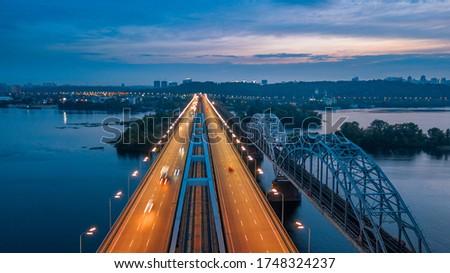 aerial night city view, luminous buildings and bridge. Drone shot.