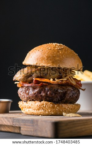 Close picture of Beautiful and succulent beef burger made of prime beef with crispy bacon and fried onion rings lay on a wooden plate in sesame bread