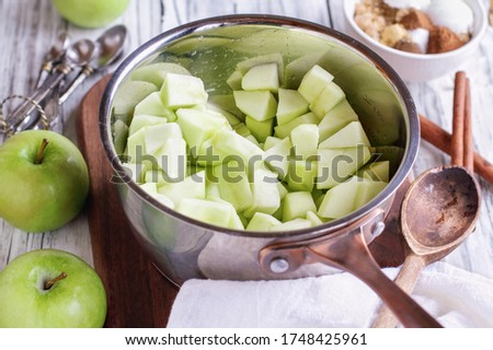 Ingredients of freshly diced Granny Smith green apples in a sauce pan with ingredients lying near by to make apple pies or tarts. Selective focus with blurred background.