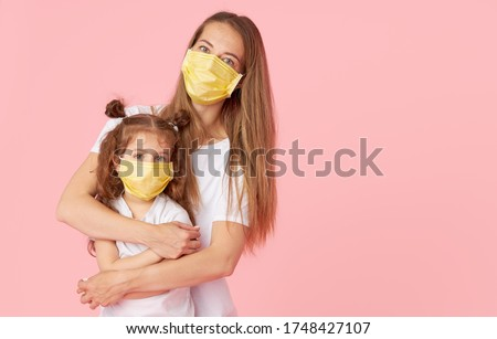 Caring for loved ones. Young mother hugs little daughter in protective medical masks during Covid-19 pandemics. Studio pink background #1748427107