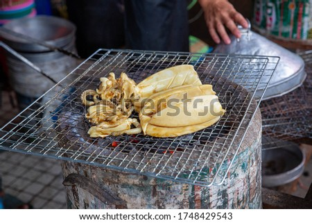Grilled Cuttlefish on a charcoal stove. Grilled squid is very tasty.Can found at street food,Thailand. BBQ Grill On Hot Charcoal.Grilled fresh squid on a grill with charcoal grill. #1748429543