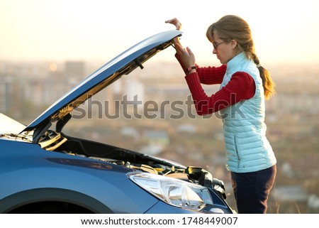 Young woman opening bonnet of broken down car having trouble with her vehicle. Female driver near auto with popped up hood. Royalty-Free Stock Photo #1748449007
