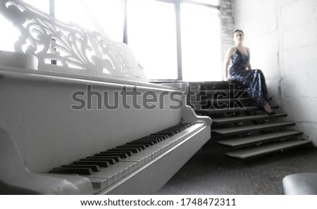 White grand piano and girl sitting in a blue dress in beautiful, classical interior before the concert