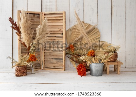 Rustic backdrop made with dried leaves and red little flowers. Royalty-Free Stock Photo #1748523368