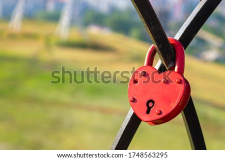 Closed red heart-shaped padlock. Symbol of eternal love. Lock of love. Tradition of lovers on the wedding day. Selective focus, copy space