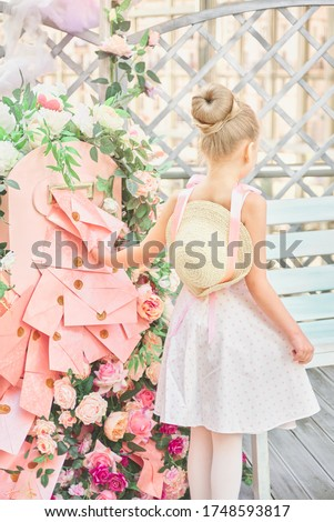 little girl with a straw hat on her back in a dress holds a pink paper envelope for letters