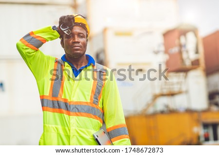 Tired stress worker sweat from hot weather in summer working in port goods cargo shipping logistic ground,  Black African race people. Royalty-Free Stock Photo #1748672873