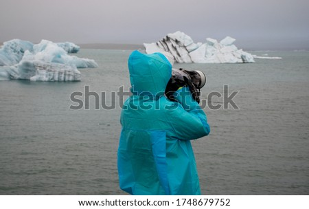 Photographer wearing a raincoat takes a picture in Jokulsarlon, Iceland with a small iceberg floating in the lake