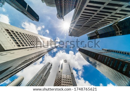 Skyscraper tower buildings in business district, Singapore city. Cloud and sun flares on sunny day sky. Low angle view. Asia financial economy, merger & acquisition, or modern architecture concept Royalty-Free Stock Photo #1748765621