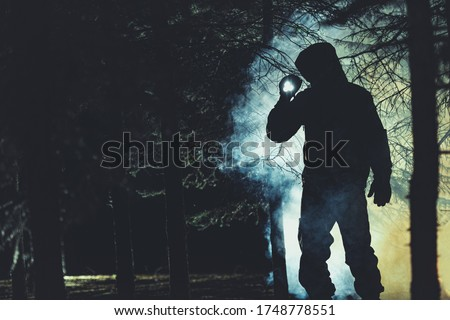 Mysterious Men with Flashlight in His Hand In Dark Foggy Forest. Poacher, Hunter or Rescuer During Rescue Action. Royalty-Free Stock Photo #1748778551