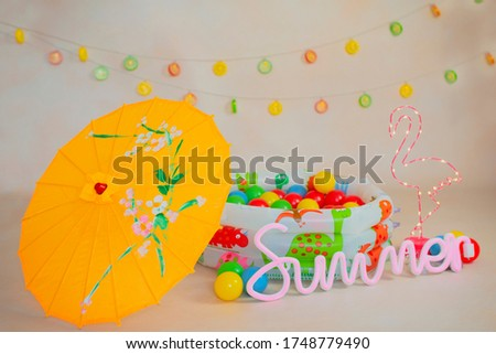 Summer photoshoot in studio for kids with ball swimming pool umbrella and pink flamingo