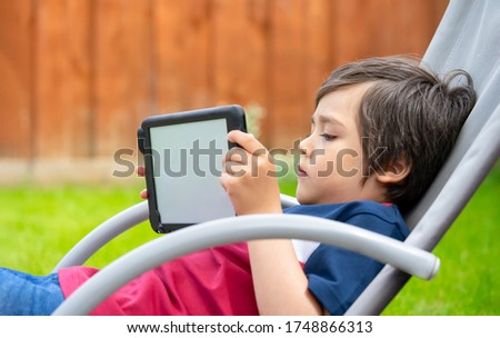 Portrait kid with playing game on tablet, A boy having fun watching cartoons on digital tablet, Child siting on rocking chair relaxing on weekend in the garden on spring or Summer, Home schooling