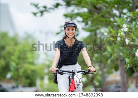 Asian woman ride bikes to work she is happy and safe. Royalty-Free Stock Photo #1748892398