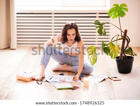 Young brunette woman creating her Feng Shui wish map using scissors. Dreams and wishes #1748926325