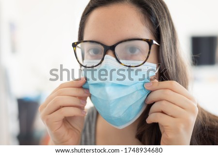 Woman wearing surgical mask due to the pandemic but its cause the fogging of the glasses. Problem of fogging of the glasses due to the wearing of the surgical mask. Royalty-Free Stock Photo #1748934680
