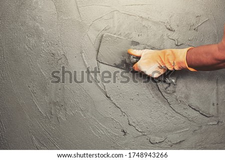 hand of worker plastering cement at wall for building house Royalty-Free Stock Photo #1748943266