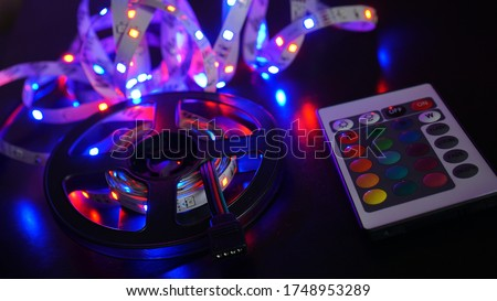 LED strip in purple colors and a control panel for switching colors. Dark background Royalty-Free Stock Photo #1748953289