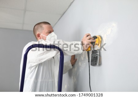 Male builder in uniform cleans wall with putty. Quality putty surfaces. Man removes an old putty with an electric tool. Repair walls, alignment before painting. Finishing putty walls apartment #1749001328
