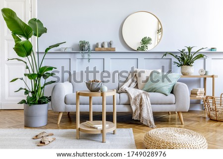 Stylish living room interior with design grey sofa, coffe table, pouf, basket, shelf, mirror, tropical plants, decoration, carpet, pillows and elegant personal accessories in modern home decor. Royalty-Free Stock Photo #1749028976