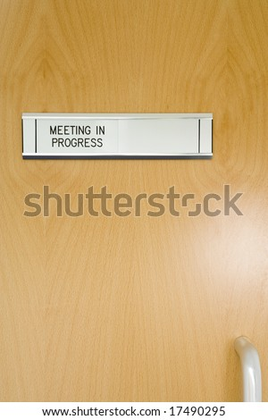 A Closed Office Door, With 'Meeting In Progress' Sign