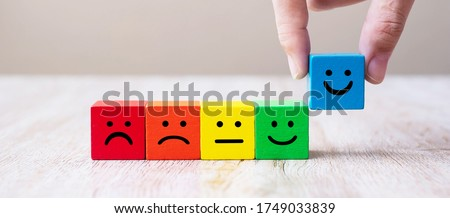 Emotion face symbol on yellow wooden cube blocks. Service rating, ranking, customer review, satisfaction and feedback concept.
