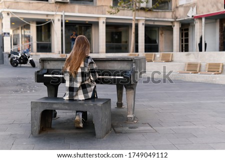 Teenage Girl with long hair plays music on the piano outdoors on Haifa street, Israel in the warm autumn evening
