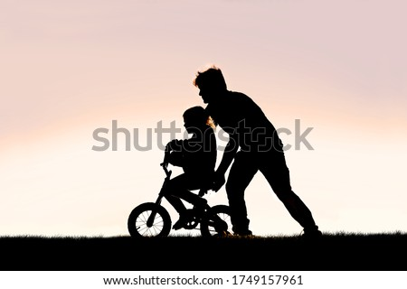 A Silhouette of a good father is helping his young girl child learn to ride her bicycle with training wheels on a summer day.