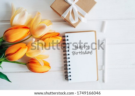 In the notebook congratulations on his birthday. Writing on the birthday page. A bouquet of orange tulips and a gift box.
