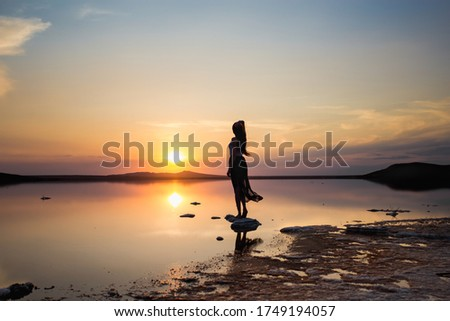 Young Woman Silhouette. Sunset on the beach #1749194057