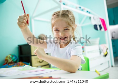 Adorable toddler girl drawing with pencils at home sitting at the table. Creative child sitting in a room learning to draw. Toddler girl doing homework at home. #1749211040