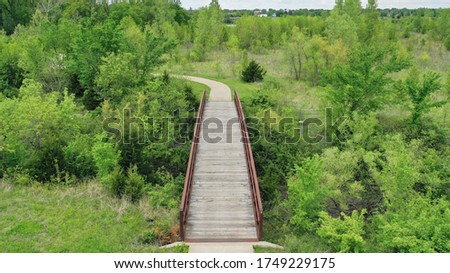 Drone images of walking, cycling, running trails in wooden, green, nature area. bridge. intersection. parks and recreation. aerial view. #1749229175