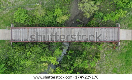 Drone images of walking, cycling, running trails in wooden, green, nature area. bridge. intersection. parks and recreation. aerial view. #1749229178