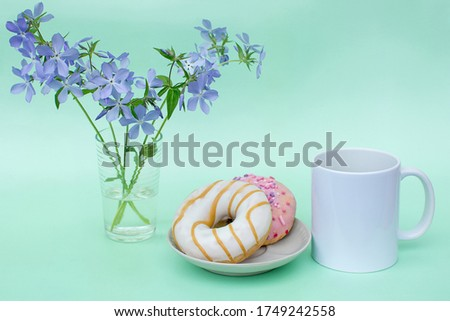 White mug without logos on mint background. There are 2 delicious doughnuts on the plate. There are blue flowers in the vase. Photos in pastel colors. The concept of the morning coffee, Breakfast