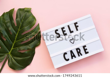 Self-care word on lightbox on pink background flat lay. Take care of yourself Royalty-Free Stock Photo #1749243611