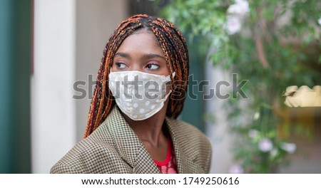 Young dark-skinned girl wearing protective fabric face mask in coronavirus pandemic, COVID-19. #1749250616