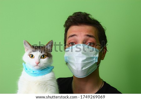 The cat in the hands of a man dressed in a surgical medical mask. Green background The concept of love and care for pets #1749269069